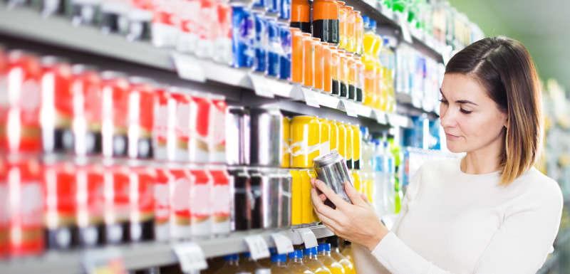 Femme tenant une cannette de soda dans un supermarché - taxe soda