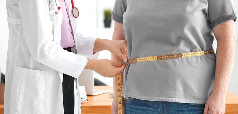 un médecin mesure le ventre d'une patiente en surpoids, espérance de vie